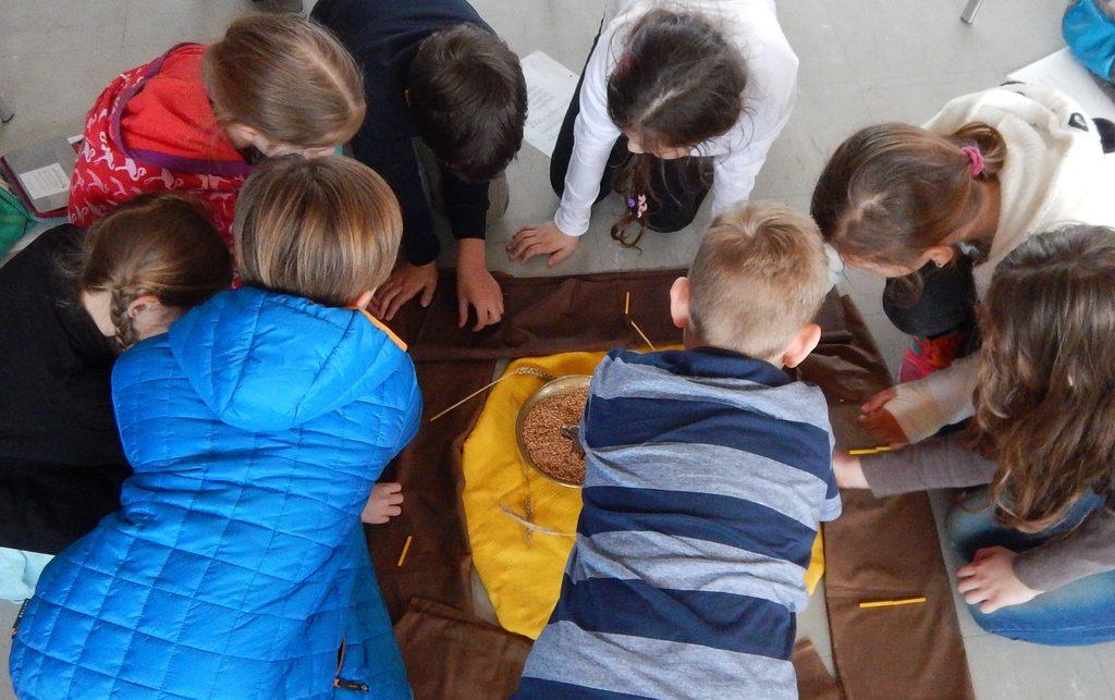 Kinder gestalten die Kreismitte mit Legematerial