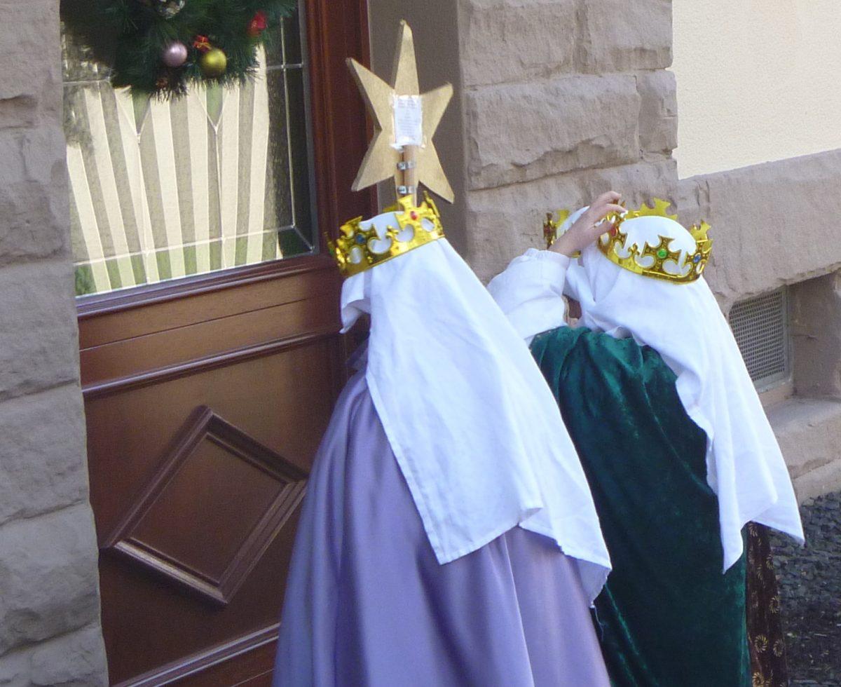 Sternsinger klingeln an einer Tür